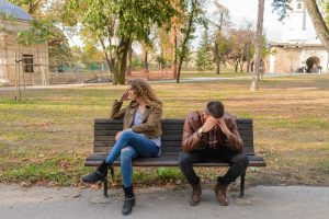 two people in a relationship sitting on park bench
