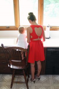 A homemaker with her child in the kitchen.
