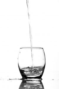 A glass of water being poured